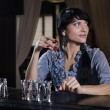Stylish young woman drinking alone at the bar — Stock Photo