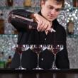 Barman mixing cocktails at the bar — Stock Photo