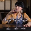 Young woman drinking alone at a bar — 图库照片