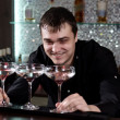 Barman grinning as he plays with three cocktails — Stock Photo