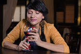 Woman holding a glass of red wine at the bar — Stockfoto