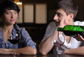 Young couple enjoying a glass of wine at the bar — Stock Photo