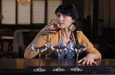 Young woman drinking alone at a bar — Stock Photo