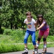 Two young women having fun rollerblading — Stock Photo