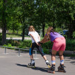 Woman being pulled along by a young roller skater — Stock Photo