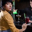 Woman sitting at a bar waiting to be served — Stock Photo