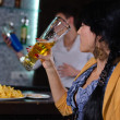 Young woman enjoying a beer at the bar — Stock Photo