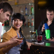 Laughing couple drinking at a pub counter — Stock Photo