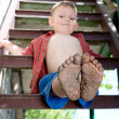 Little boy showing off his dirty feet — Stock Photo #36516179
