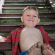 Little boy showing off his dirty feet — Stock Photo #36516183