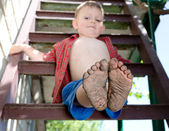 Little boy showing off his dirty feet — Stock Photo