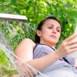 Stock Photo: Womreading whilst relaxing in hammock