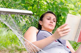 Woman reading whilst relaxing in a hammock — Stock Photo