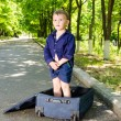 Cute young boy standing in an open suitcase — Stock Photo #37814287