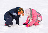 Young brother and sister playing in the snow — Stock Photo