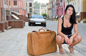 Young woman crouching alongside a suitcase — Stok fotoğraf