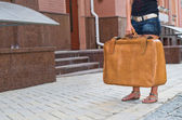 Woman waiting with her suitcase in the street — Stock Photo