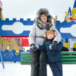 Smiling mother and son in a winter playground — Stock Photo