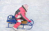 Little girl in pink playing on a toboggan — Stock Photo