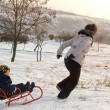 Mother running through the snow with a sled — Stock Photo #38397991