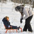 Mother and son tobogganing in the snow — Stock Photo