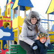 Happy mother and son in a winter playground — Stock Photo