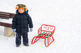 Little boy in the snow with his toboggan — Stock Photo