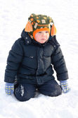 Cute small boy kneeling in winter snow — Stock Photo