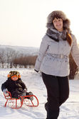 Mother pulling a toboggan with her child in snow — Stock Photo