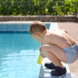 Young boy playing at the edge of a swimming pool — Stock Photo