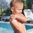 Постер, плакат: Little boy applying suntan lotion to his skin
