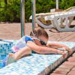 Stock Photo: Small boy clambering out of swimming pool