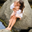 Young mother and her son sitting on a rock — Stock Photo