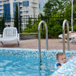 Little boy in a pool hanging onto the edge — Stock Photo