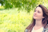 Beautiful young woman daydreaming in a park — Stock Photo