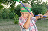 Cute little boy holding onto a purple rope — Stock Photo