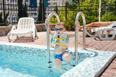 Small boy clambering out of a swimming pool — Stock Photo