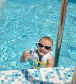 Goung feliz rapaz em uma piscina dando um polegar para — Fotografia Stock