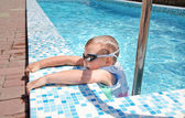 Small boy clambering out swimming pool — Stock Photo