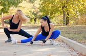 Two fit athletic woman working out in a park — Stock Photo