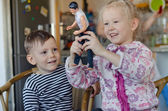 Happy little girl and boy playing with a doll — Stockfoto