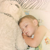 Cute little boy sleeping with his teddy bear — Stock Photo