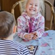 Beautiful laughing little girl playing checkers — Stockfoto