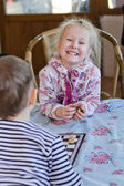 Beautiful laughing little girl playing checkers — Stock Photo