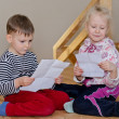 Little boy and girl sitting together reading — Stock Photo #44155983