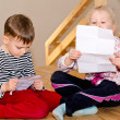 Little boy and girl sitting together reading — Stock Photo #44156217