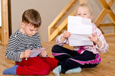 Little boy and girl sitting together reading — Stock Photo