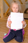Pretty little blond girl sitting reading a letter — Stock Photo