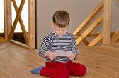 Little boy kneeling on the floor reading — Stock Photo