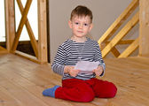 Little boy kneeling on the floor reading — Stock Photo